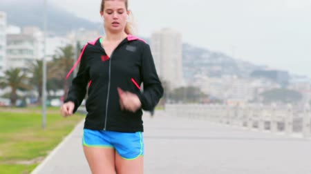 corrida : Pretty young determined woman running at promenade