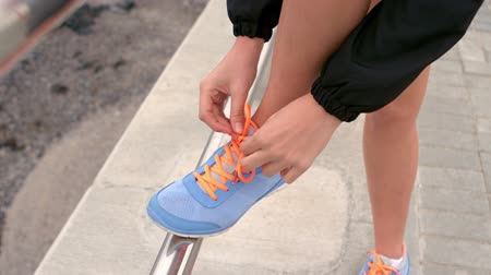 tying : Woman tying up her shoe laces on the pier Stock Footage