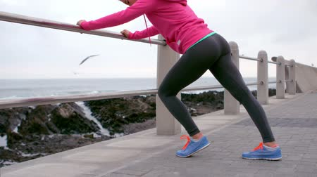 atletika : Fit woman stretching leg on railing at promenade