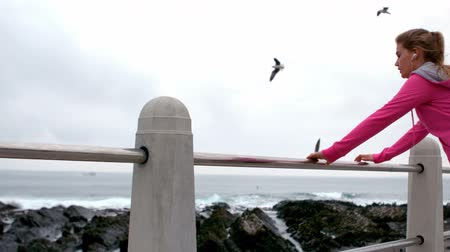 atletismo : Fit woman stretching leg on railing at promenade