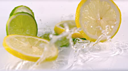 фрукты : Close up view of lemon slices falling into water