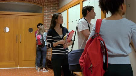 aluno : Few students chatting in hallway in college