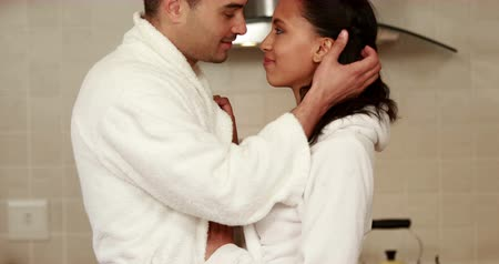ношение : Lovely couple wearing bathrobe smiling at camera in kitchen