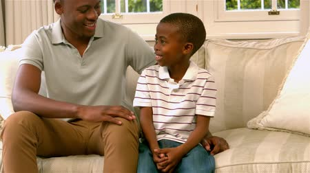 family life : Father and son talking on sofa in slow motion