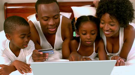 family life : Black family on bed with laptop and credit card rejoicing in slow motion Stock Footage