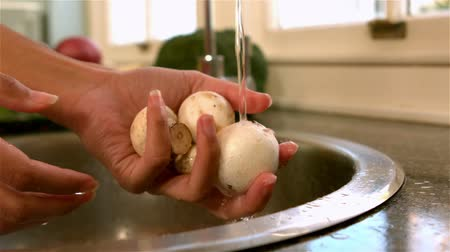 highspeed : Woman washing mushrooms in kitchen in slow motion