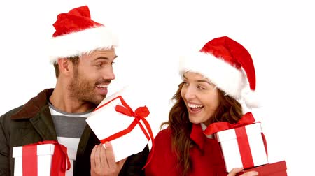 highspeed : Attractive young couple wearing santa hats with gift against white background