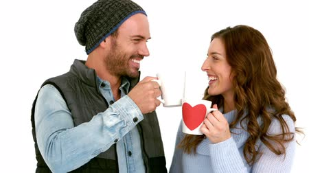 ugró : Attractive young couple in warm clothes holding mugs against white background