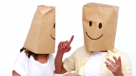 head over : Couple with cardboard bag over their head against white background