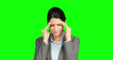 apprehensive : Worried businesswoman holding her head against green background Stock Footage