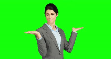 деловая женщина : Pretty businesswoman presenting something against green background