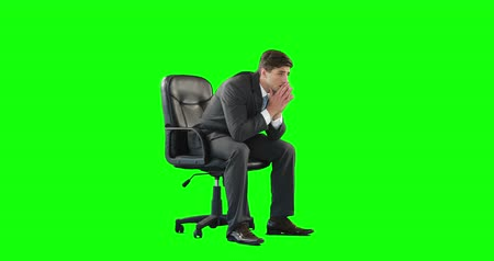 apprehensive : Young businessman getting a headache against green background