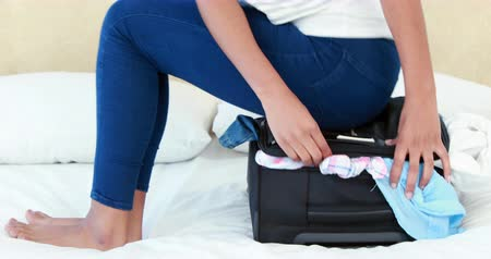 bagagem : Woman sitting on her luggage on bed