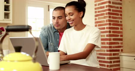 home life : Happy couple using laptop in the kitchen