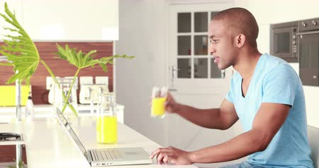 cotidiano : Casual smiling man drinking orange juice in the kitchen
