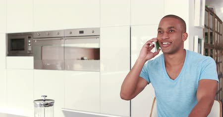 telefone celular : Smiling young man having a phone call in the kitchen