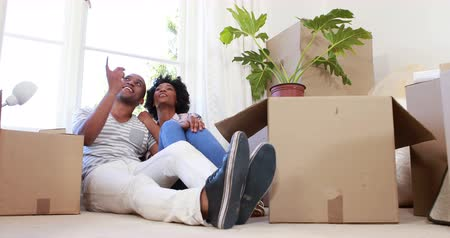 abertura : Smiling couple unpacking cardboard boxes in their new home