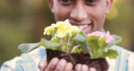 ature : Happy gardener holding a plant in garden Stock Footage
