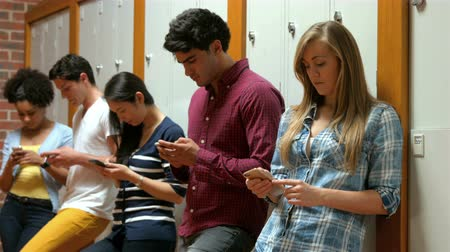 прихожая : Students on their smartphone leaning on lockers in college