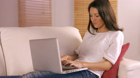 website : Smiling woman using laptop on sofa in the living room Stock Footage
