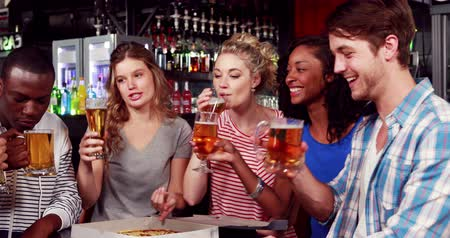 bares : Happy friends toasting with beer in bar
