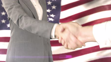 рукопожатие : Digital composite of Business handshake against american flag Стоковые видеозаписи
