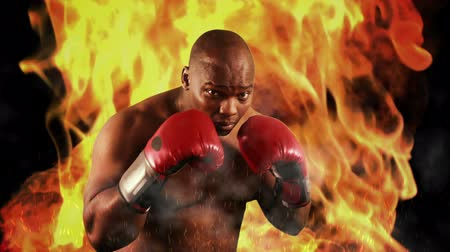 duruş : Tough boxer punching with red gloves on flaming background Stok Video