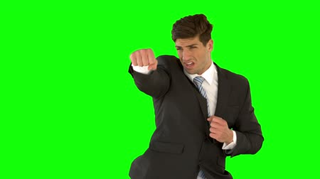 puncs : Businessman punching on green screen in slow motion