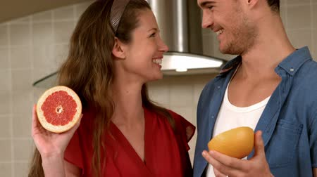 grejpfrut : Smiling young couple holding half of grapefruit in the kitchen Wideo