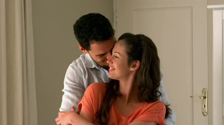 объятие : Loving couple embracing and hugging at home