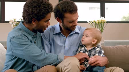 гей : Gay smiling couple with their kid in living room