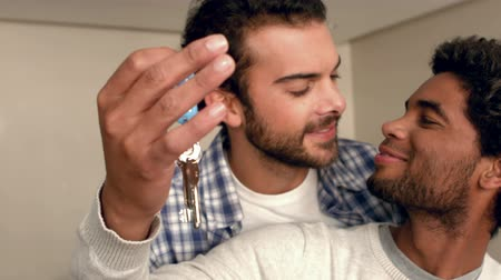 home life : Happy homosexual couple holding key in new home
