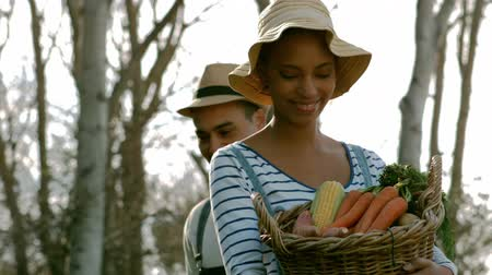 self sufficiency : Happy young couple with box of vegetables in garden