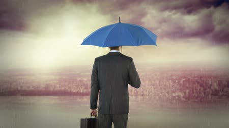 стоять : rear view of businessman holding umbrella under a storm Стоковые видеозаписи