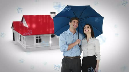bizneswoman : Composite image of businessman and businesswoman holding an umbrella against house