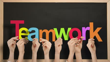 teamwork : Hands holding up teamwork against chalkboard Stock Footage