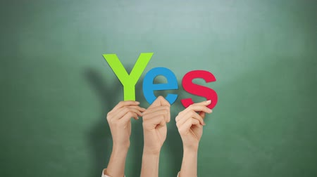 igen : Hands holding up yes against chalkboard