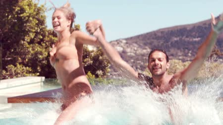 salto : Couple jumping into swimming pool holding hands in slow motion Stock Footage