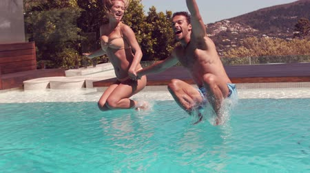 jump : Couple jumping into swimming pool holding hands in slow motion Stock Footage