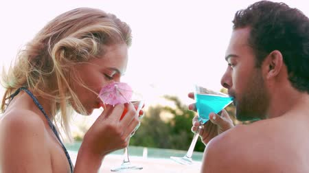 içme : Attractive couple relaxing by the pool in slow motion