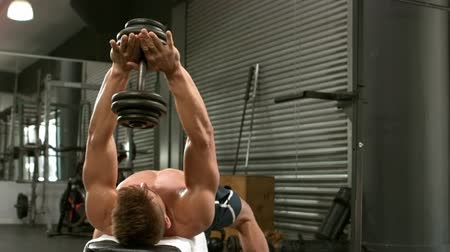 мышцы : Fit man lifting dumbbells lying on the bench in crossfit