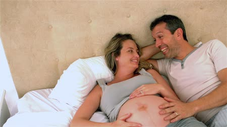 dokunaklı : Happy future parents talking on bed and touching belly at home Stok Video