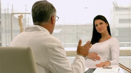 maternity hospital : Doctor and pregnant woman talking in office