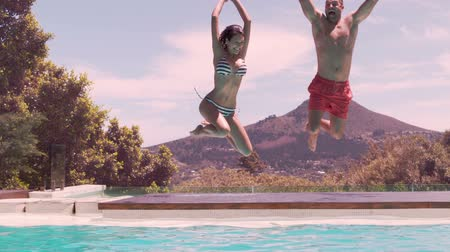 jump : Happy couple jumping in the swimming pool in slow motion