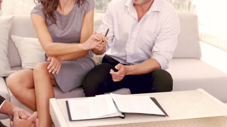 anlaşma : Smiling couple signing contract for new house in slow motion