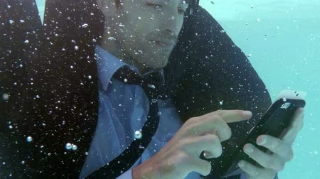 poça de água : Businessman using smartphone underwater in slow motion