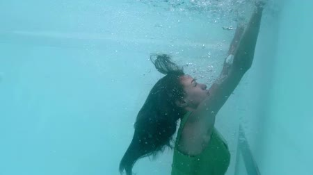 swimming underwater : Beautiful woman with green dress swimming underwater in slow motion