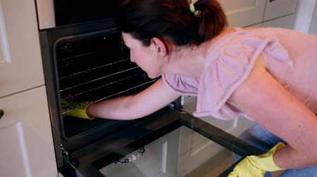cleaning products : Woman cleaning the oven at home in the kitchen Stock Footage