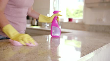cleaning products : Woman wiping the counter at home in the kitchen
