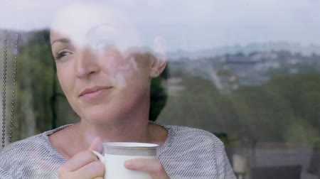 double happiness : Thoughtful woman enjoying a coffee at home in the kitchen Stock Footage